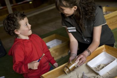 Child and a National Trust Visitor Services Assistant in the museum at Avebury, Wiltshire.